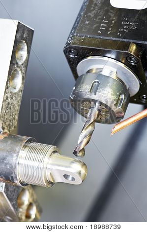 Close up industrial metal machining cutting process ? blank detail drilling
