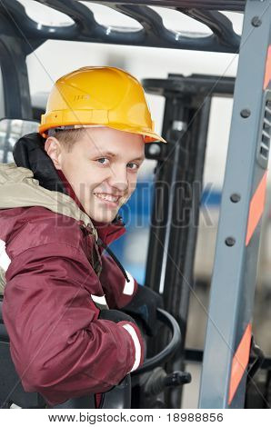 young smiley warehouse worker driver in uniform driving forklift stacker