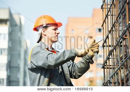 builder worker knitting metal rods bars into framework reinforcement for concrete pouring at construction site