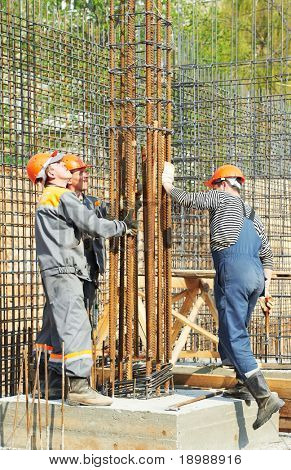 builder workers installing metal rods bars into framework reinforcement for concrete pouring at construction site