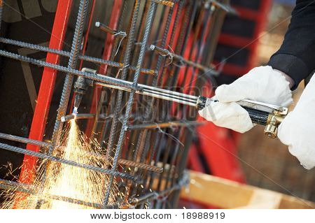 close-up worker hands in protective gloves cutting concrete reinforcing metal rods at construction site by gas flame