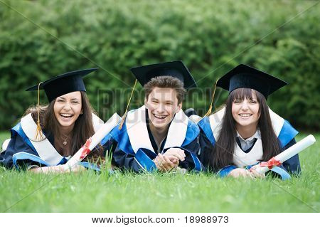 group of three graduation students lying in the park cheerful and happy