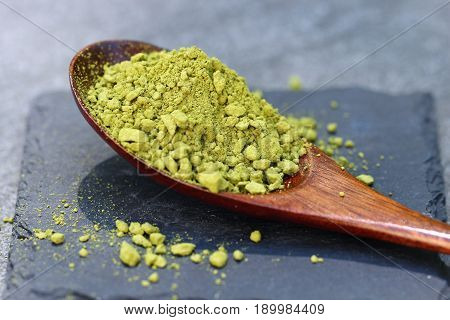 Green Matcha powder in a spoon on a slate colored tile selective focus.
