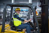 Portrait of smiling factory worker driving forklift in factory poster