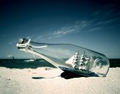 foto of shipwreck  - Bottle with ship inside lying on the beach - JPG