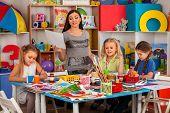 Kids playroom organization of children painting and drawing in kids club. Craft lesson in primary s poster