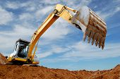 stock photo of power-shovel  - Excavator standing in sandpit with raised bucket over cloudscape sky - JPG