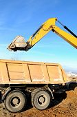 stock photo of boom-truck  - Excavator loading dump truck tipper at open cast over blue sky in winter - JPG