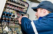 foto of electrician  - One electrician working on a industrial panel mounting - JPG