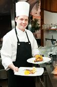 professional chef with prepared food on plates in commercial kitchen