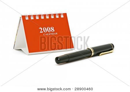 Mini desk top calender and fountain pen isolated on white background