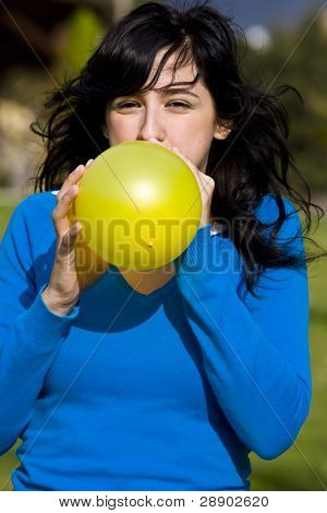Teen inflating yellow balloon