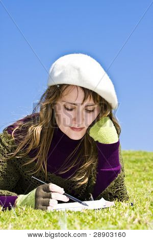 Woman painting on the grass.