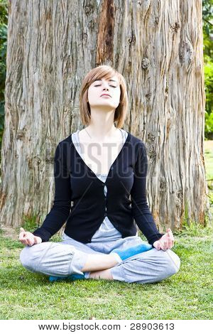 Young woman meditating in front of a tree trunk.