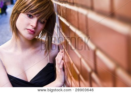 Young elegantly dressed woman on brick wall
