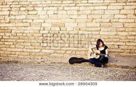Street artist playing guitar on the wall