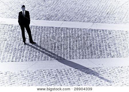 Long businessman shadow in urban background.