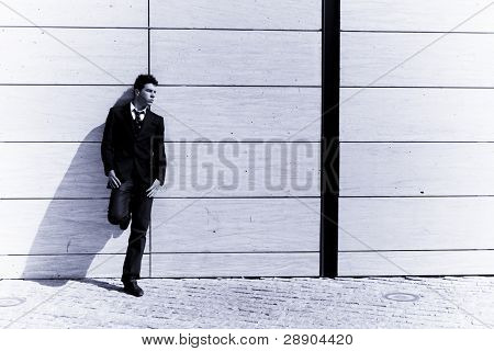 Lone businessman posing on wall, blue toned.
