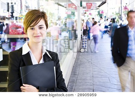 Young businesswoman over urban background, blurred citizens.