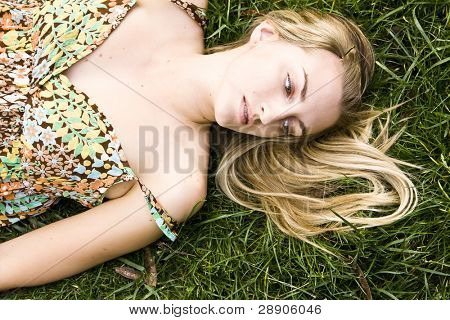 Green eyed blonde over the grass
