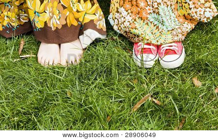 Woman feets under dress over the grass