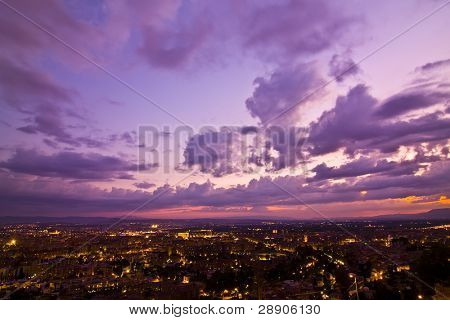 Anonymous city at sunset under cloudscape