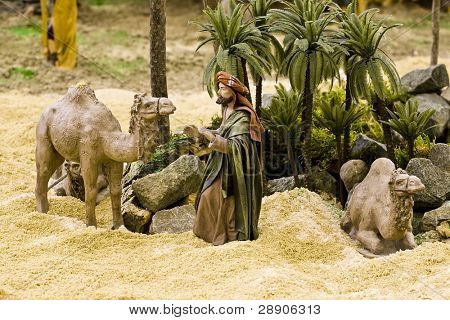 Arabic man with camels, figurines in a crib scene.