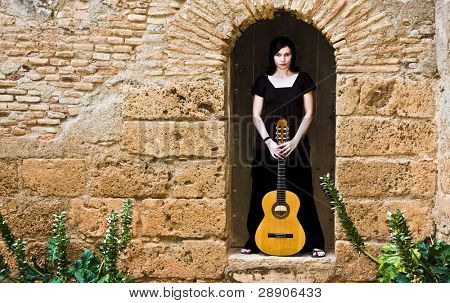 Young guitar performer posing over antique background