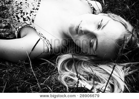 Young blonde over the grass in black and white.