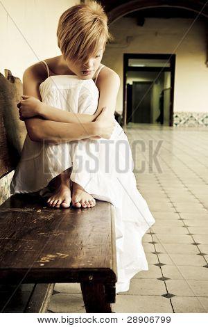 Mujer solitaria en Banco de fondo sucio.
