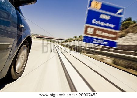 Road signs blurred due the vehicle high speed.