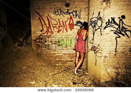 Sad young girl in a dirty location