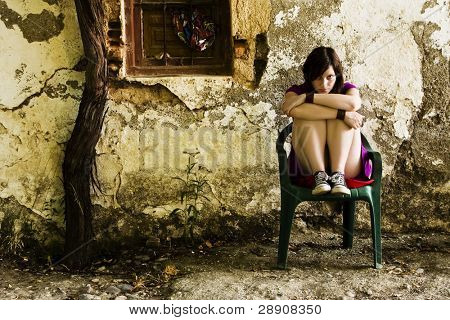 Young sad woman sitting in old dirty place