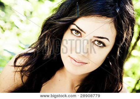 Beautiful woman with impressive green eyes staring at camera.