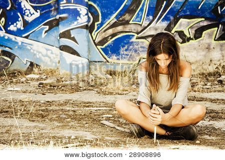 Young sitting pensive woman armed with a knife.