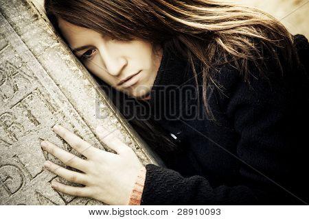 Sad woman embracing a grave.