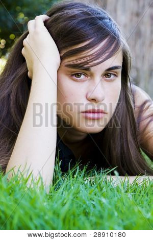 Young staring woman laying on the grass