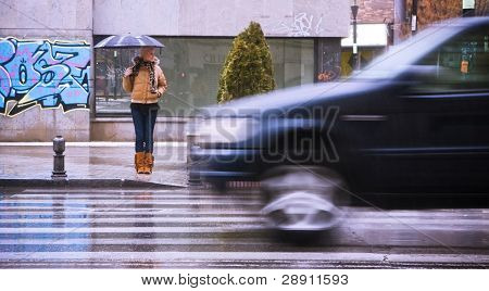 Young blonde waiting for the traffic stop under rain