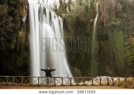 Male traveler feeling freedom under huge waterfall.