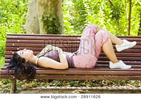 Beautiful woman dreaming after reading in a park bench.
