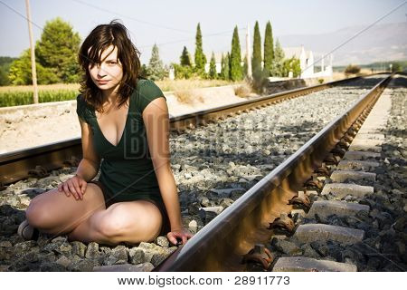 Young beautiful woman sitting on railtrack