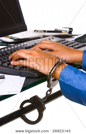 An employee's hand locked into the work desk, the usually description for today employee who always locked into their work. And may be can have another description about cyberycrime.