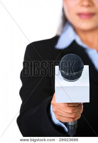 A female host is holding a microphone pointed directly to the camera. Shot against white background.