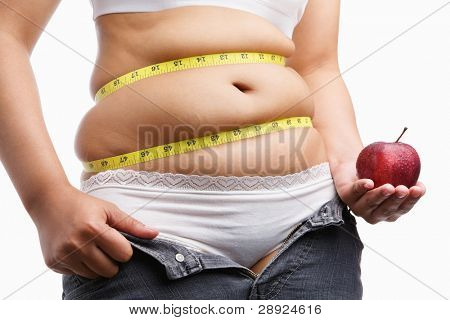 fat woman with unzip jeans holding apple, a concept to fight obesity by starting diet