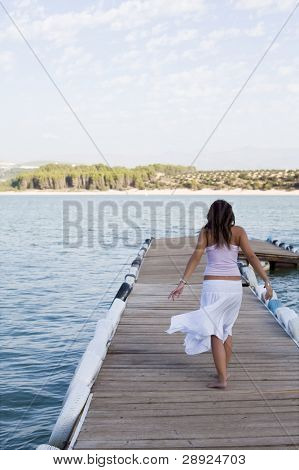 Young beautiful woman walking on pier