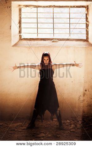 Arms raised young beautiful gothic girl on dirty place.