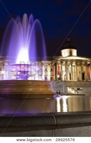 National Gallery behind colored fountain at Trafalgar Square.