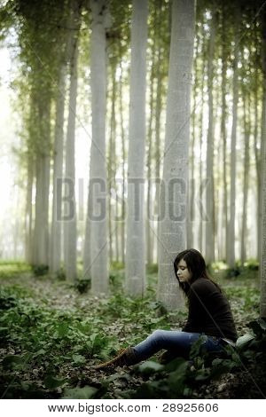 Young beautiful thoughtful girl sitting on the forest