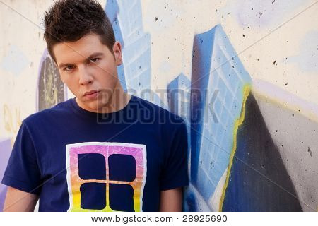 Young man portrait over grafted wall.