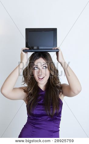 Sexy young beautiful woman with mini laptop over her head.
